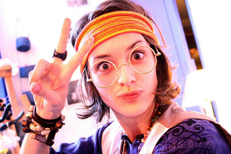 A photo of a woman dressed up as a hippy with colourful bandana, sunglasses and two fingers victory sign.