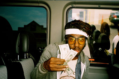 A photograph of a man on a bus holding cash with big hair, headband and big glasses