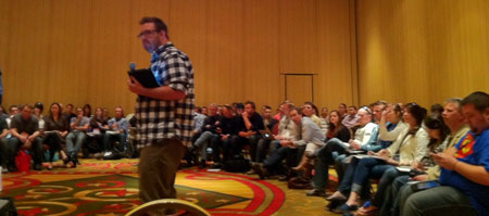 A photograph of Brett Harned presenting his talk at the 2011 SXSW event surrounded by a circular row of audience members