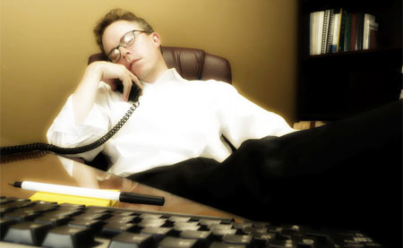 An office worker asleep while on the phone