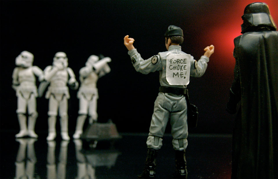 "A photo of Star Wars toys showing Stormtroopers laughing at a Death Star worker who has a sign on his back saying ""Force Choke Me"" with Darth Vader looking on."