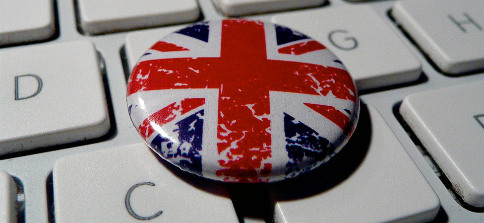 A photo of a little Union Jack circular button bade resting on a Mac-style keyboard.