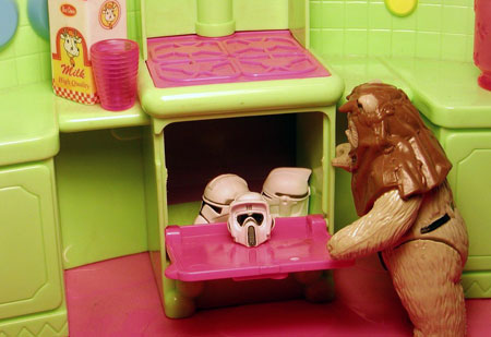 An image of a toy Star Wars Ewok placing the heads of other Star Wars figures in a toy oven cooker