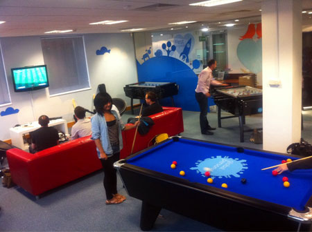 A photograph of the globaldev games room in use with pool table, football tables and Xbox
