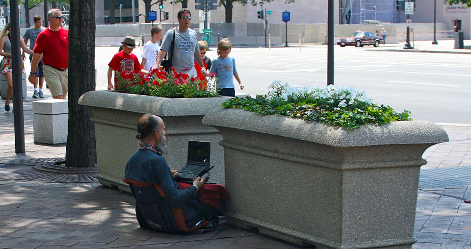 A photo of an old man with a pony tail sitting in the street with a laptop open.