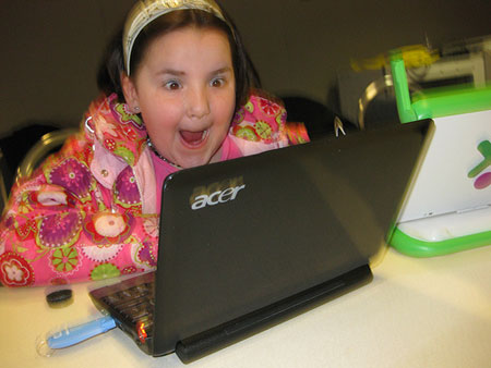 Photograph of a young girl looking at an open laptop looking insanely enthusiastic