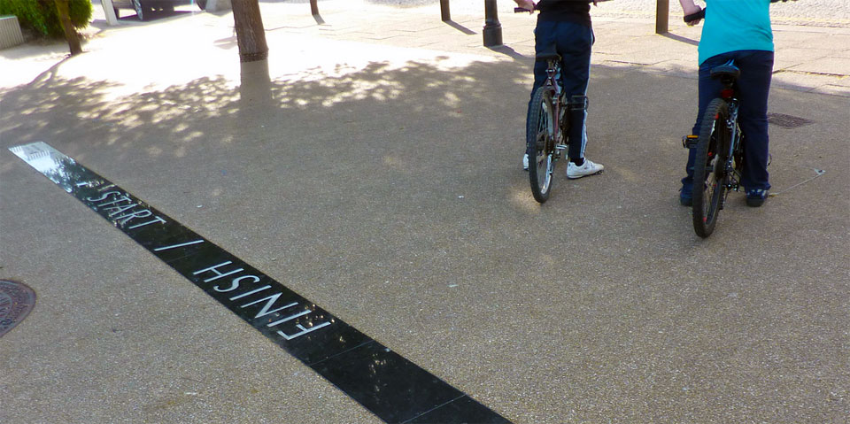 A photograph showing the back of two children on BMX bikes with a crude black start and finish line on a concrete road floor.