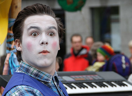 Photo of a street entertainer with white make-up on looking stunned.