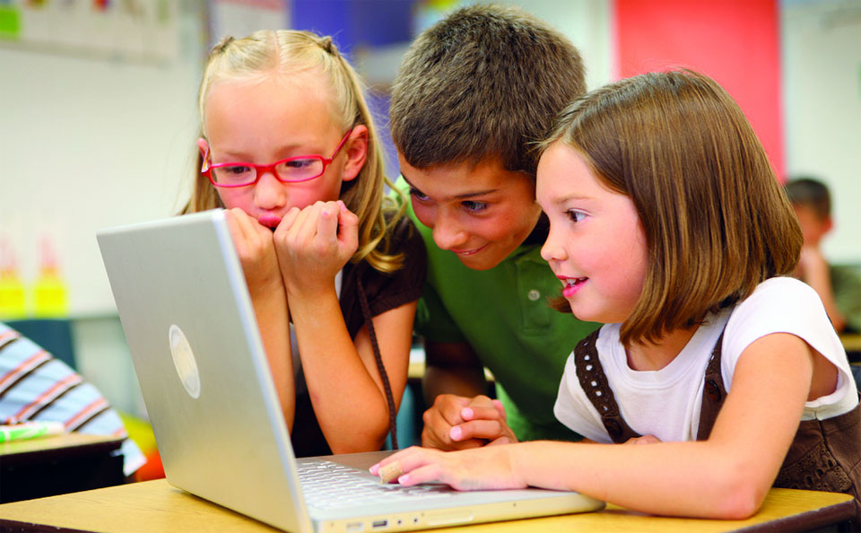 A photo of three children smiling and grouped around a laptop.