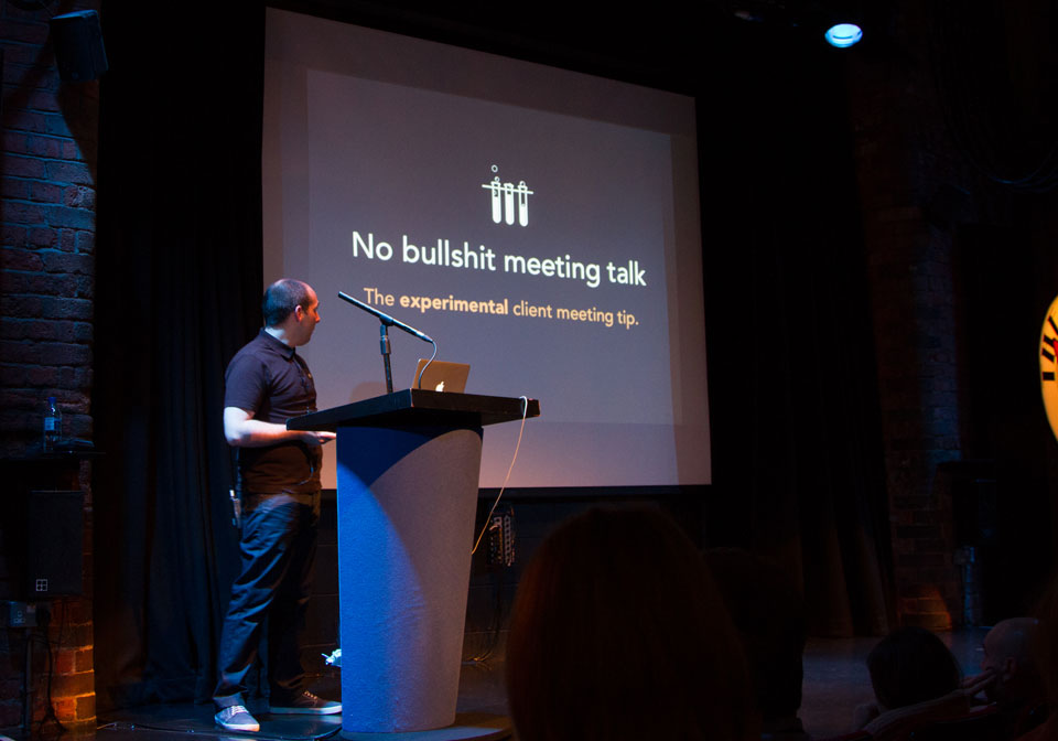A photo of Sam on stage behind a lectern in front of one of his slides that says No bullshit meeting talk.
