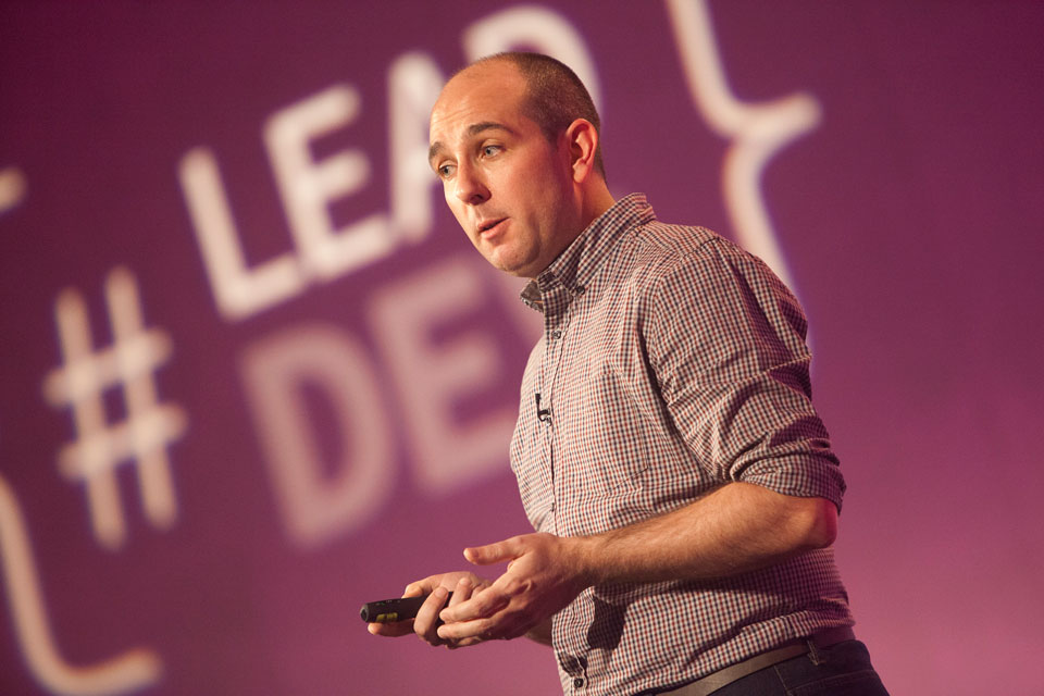 A photo of Sam Barnes on stage in a shirt, against a purple background with the lead developer event logo in the background, clicker in hand and visibly mid-sentence.