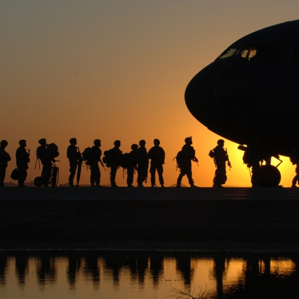A photo taken during an orange sunset, showing the silhouettes of soldiers, lining up to board a plane, which is seen on the right-hand side of the picture.