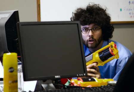 A photograph of an office worker with glasses and an afro style hairstyle peeking out behind a monitor with a toy gun