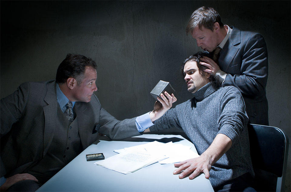 A photo of a staged interrogation scene with one man holding a box to the face of a man while another holds the head of the man who looks distressed
