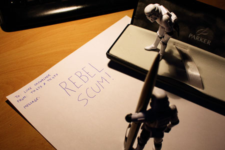 An image of two Star Wars Stormtrooper toy figures penning a letter to Luke Skywalker saying Rebel Scum