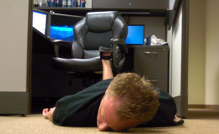 An image of a web project manager fallen face first off his chair onto the floor.