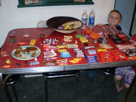 A photograph showing a young boy who has lined up all of his sweets in perfect order