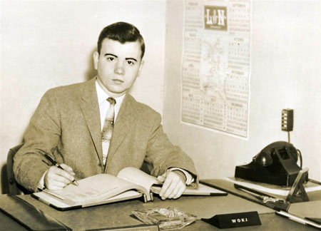 A yellow with age photograph of a young man in a suit at his office desk in the 1950s
