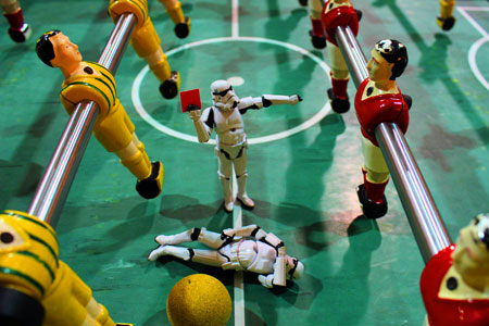 An image of one Star Wars Stormtrooper toy on a table football pitching holding up a red card to table football man, while another Stormtrooper toy lay on the floor injured.