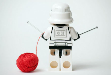 An image of a lego Star Wars Stormtropper from behind who is knitting with needles and a red ball of wool