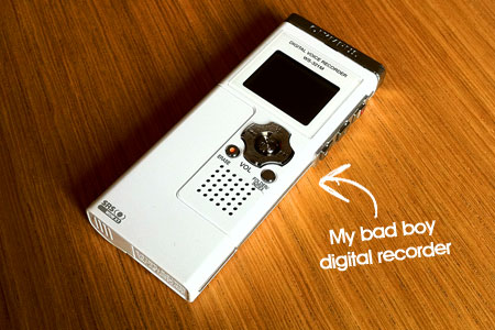 A picture of a white digital voice recorder on a wooden surface