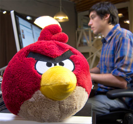 A photograph of an Angry Bird toy from the popular iOS game series looking angry with a web designer in the background