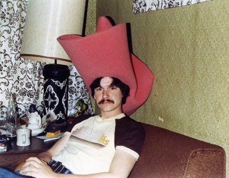 A 1970's style photograph of a man with an oversized foam cowboy hat on sitting on the sofa