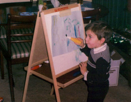 An old photograph of Sam Barnes as a child painting a bad picture on a child's standing upright easel