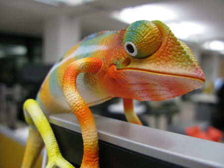 A photo of a toy chameleon perched on top of a computer monitor in an office