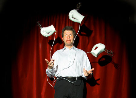 A photograph of a man in a shirt and trousers juggling three handheld food blenders lit by a stage spotlight in front of a red stage-like curtain