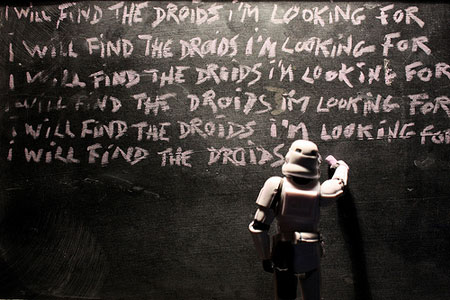 A photograph of a Stormtrooper toy writing lines on a blackboard saying I will find the Droids over and over as if in detention at school