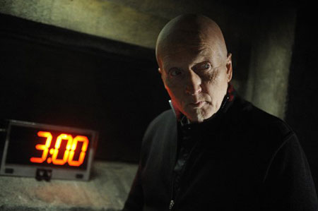 A movie screenshot of Jigsaw with a menacing stare in front of a countdown clock