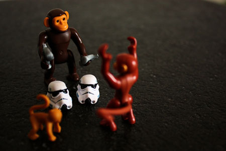 A picture of two toy monkeys playing with the head of a Stormtrooper toy