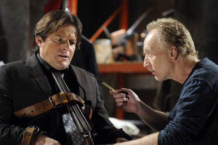 A movie screenshot of Jigsaw talking to Detective Hoffman as he is tied to a chair with a shotgun pointed at himself