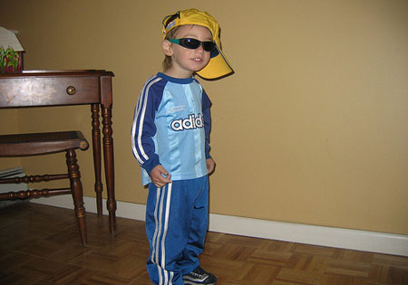 A photo of a young boy dressed up as a little gangster rap artist