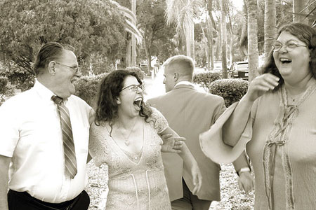 An old sepia picture of a man and two women in hysterics with laughter