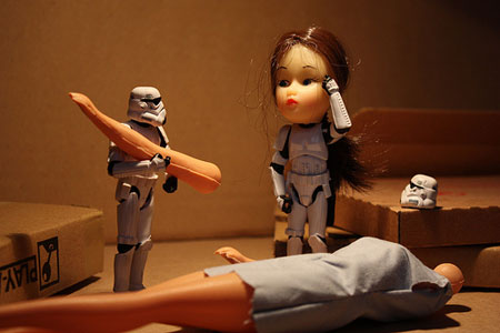 A picture of two Star Wars Stormtrooper toy figures, one with the head of a child's doll while scratching his head in confusion