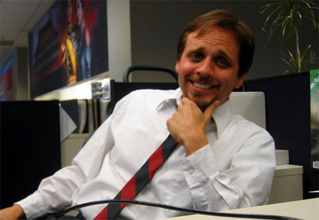 Image of a very smarmy looking manager smiling while sitting at a desk with his chin resting on his hands
