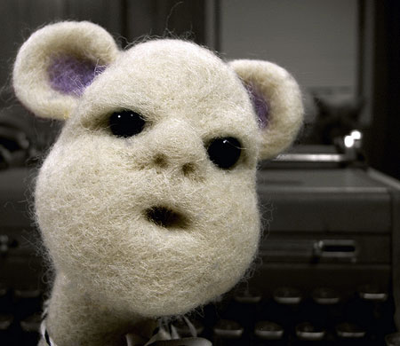 A photograph of a white furry-faced toy with a gormless look on his face