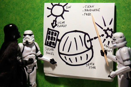 An image showing two Star Wars toy Stormtroopers presenting an idea on a whiteboard for a solar powered Death Star to toy Darth Vader toy figure
