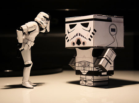 An image of a toy Star Wars Stormtrooper looking at a basic cardboard version of a Stormtrooper